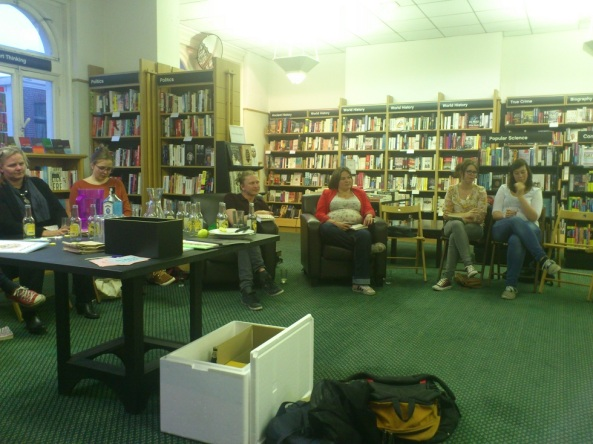 Impressiefoto van de leesclub met de schrijver, Joe Dunthorne, in het midden, halfverborgen achter de tafel met gin en tonic en bier.